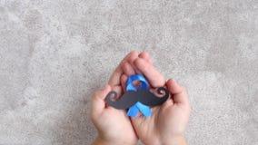 Modelo del bigote con símbolo de la cinta azul en manos del ` s del niño concepto del movember Conciencia de la salud del ` s del