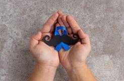 Modelo del bigote con símbolo de la cinta azul Movember de noviembre concentrado imagen de archivo