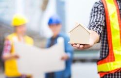 Modelo del casa o casero con el trabajo en equipo del éxito del ingeniero civil concentrado fotos de archivo libres de regalías