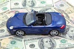 Modelo del coche deportivo en la pila de billetes de banco del dólar de EE. UU. Fotografía de archivo libre de regalías