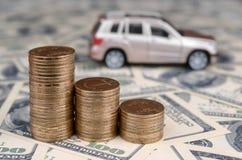 Modelo del coche del juguete en las pilas de mentiras de oro de las monedas en muchos billetes de dólar fotografía de archivo