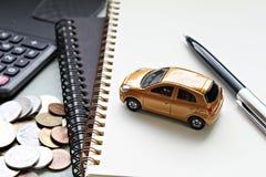 Modelo del coche, pluma, papeles del cuaderno, calculadora y monedas miniatura en la tabla de la oficina Fotografía de archivo libre de regalías