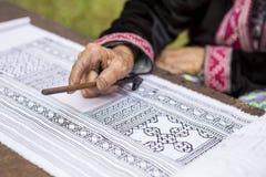 Modelo del dibujo de la mano de la señora mayor en la tela blanca con la cera caliente negra Fotos de archivo