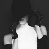 Modelo del encanto en fondo negro en guantes de moda y otoño del sombrero Imagenes de archivo