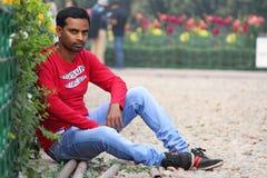Modelo del hombre joven que se sienta en un jardín con vaqueros y la camiseta que llevan imágenes de archivo libres de regalías