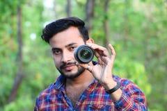 Modelo del hombre joven que sostiene una lente de cámara delante de su cara con el foco imagen de archivo libre de regalías