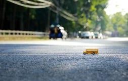 Modelo del juguete del autobús escolar en el camino Fotografía de archivo libre de regalías