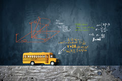 Modelo del juguete del autobús escolar y formular de la matemáticas Foto de archivo libre de regalías