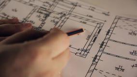 Modelo del plan arquitectónico que señala con el lápiz metrajes
