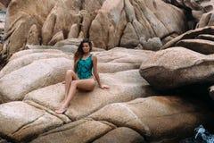 Modelo delgado atractivo con las piernas largas que toman el sol en una piedra plana grande en la playa, tomando el sol fotografía de archivo libre de regalías