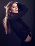 Modelo delgado femenino atractivo que presenta en camisa negra con styl largo del pelo Foto de archivo