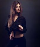 Modelo delgado femenino atractivo que presenta en camisa negra e ingenio negro de los vaqueros Fotos de archivo libres de regalías
