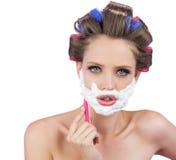 Modelo delicioso en los bigudíes de pelo que presentan con la maquinilla de afeitar Fotografía de archivo libre de regalías