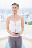 Modelo deportivo sonriente que escucha la música Imágenes de archivo libres de regalías