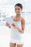 Modelo deportivo sonriente que sostiene la tableta digital Imagen de archivo libre de regalías
