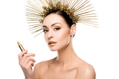Modelo desnudo atractivo en el casco de oro que sostiene el lápiz labial Fotografía de archivo