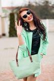 Modelo divertido en gafas de sol y en un poco vestido verde, fondo blanco Retrato de la forma de vida de la moda de feliz joven Imagen de archivo libre de regalías