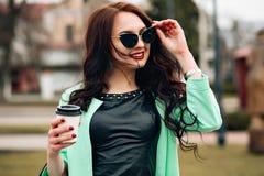 Modelo divertido en gafas de sol y en un poco vestido verde, fondo blanco Retrato de la forma de vida de la moda de feliz joven Fotografía de archivo libre de regalías