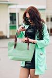 Modelo divertido en gafas de sol y en un poco vestido verde, fondo blanco Retrato de la forma de vida de la moda de feliz joven Imagenes de archivo