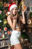 Modelo divertido joven con los ojos oscuros, el pelo marrón y el sombrero de santa celebrando Año Nuevo en casa Imágenes de archivo libres de regalías
