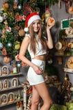 Modelo divertido joven con los ojos oscuros, el pelo marrón y el sombrero de santa celebrando Año Nuevo en casa Imagenes de archivo