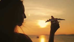 Modelo do avião da terra arrendada da silhueta da menina em sua mão durante o por do sol no mar Conceito de pensamento da ideia filme