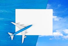 Modelo do avião e da folha de papel vazia no fundo de madeira azul conceito do curso imagens de stock