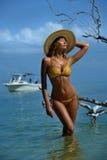 Modelo do biquini no levantamento do chapéu de palha 'sexy' na frente da câmera no lugar tropical da praia Foto de Stock Royalty Free