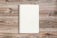 Modelo do bloco de notas aberto com a página vazia no fundo de madeira foto de stock