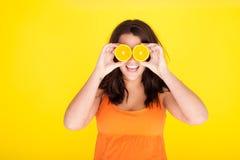 Modelo do conceito do divertimento com fatias alaranjadas para os olhos Fotografia de Stock Royalty Free
