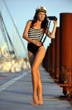 Modelo do marinheiro no roupa de banho à moda que guarda binóculos e posição no cais de madeira Imagem de Stock