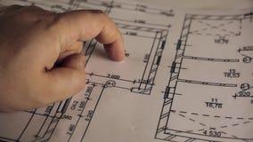 Modelo do plano arquitetónico que aponta com mão filme