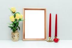 Modelo do quadro A4 de madeira com flores e velas vermelhas Fotografia de Stock Royalty Free