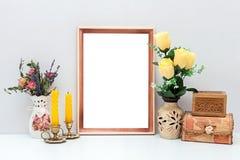 Modelo do quadro A4 de madeira com flores, velas e as caixas amarelas Fotos de Stock