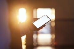 Modelo do smartphone na mão do indivíduo contra o por do sol imagem de stock royalty free