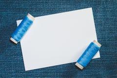 Modelo e carretéis brancos de linhas azuis do algodão no fundo da sarja de Nimes fotos de stock