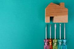Modelo e chave de fenda de madeira da casa no fundo verde Manutenção da casa, conceito da construção da casa foto de stock