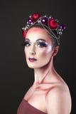 Modelo elegante con maquillaje brillante del ` s Eve del Año Nuevo en una guirnalda de Foto de archivo