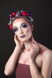 Modelo elegante con maquillaje brillante del ` s Eve del Año Nuevo en una guirnalda de Imagen de archivo
