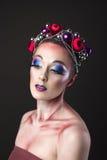 Modelo elegante con maquillaje brillante del ` s Eve del Año Nuevo en una guirnalda de Fotografía de archivo libre de regalías