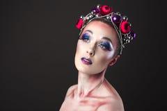 Modelo elegante con maquillaje brillante del ` s Eve del Año Nuevo en una guirnalda de Fotos de archivo libres de regalías