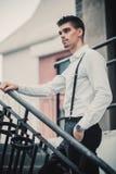 Modelo elegante joven del hombre en la ropa clásica que presenta cerca de las escaleras Tiro de la manera Imagen de archivo