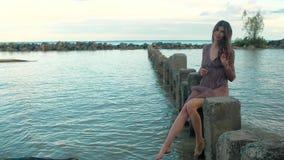 Modelo em um vestido transparente, sentando-se nas colunas de pedra que estão na água do mar video estoque