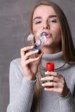 Modelo en burbujas que soplan del jersey Cierre para arriba Fondo gris Imágenes de archivo libres de regalías