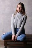 Modelo en el suéter que se sienta en una cubierta Fondo gris Imágenes de archivo libres de regalías