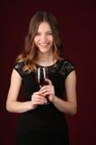 Modelo en el vestido que sostiene el vidrio de vino Cierre para arriba Fondo rojo oscuro Foto de archivo libre de regalías