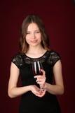 Modelo en el vestido que sostiene la copa Cierre para arriba Fondo rojo oscuro Fotografía de archivo