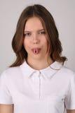 Modelo en la camiseta que muestra su lengua Cierre para arriba Fondo blanco Imagenes de archivo