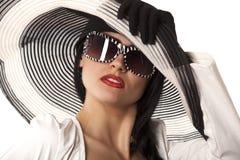 Modelo en sombrero y sunglasse rayados Foto de archivo