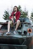 Modelo encantador con el arma que se sienta en el tanque Fotos de archivo